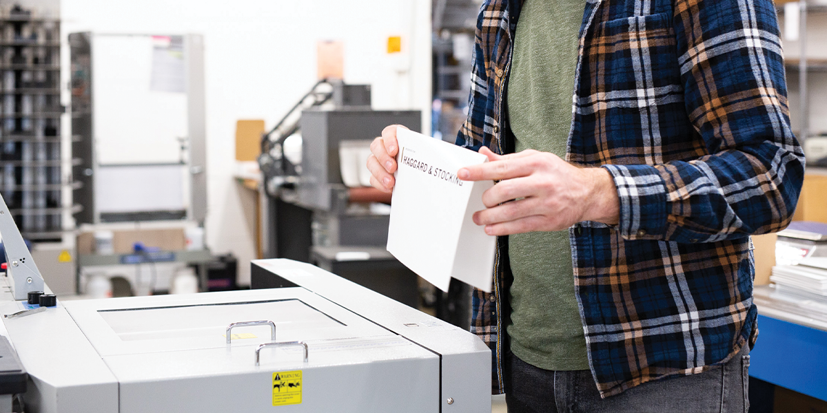 Print worker folds paper while standing at a printing press