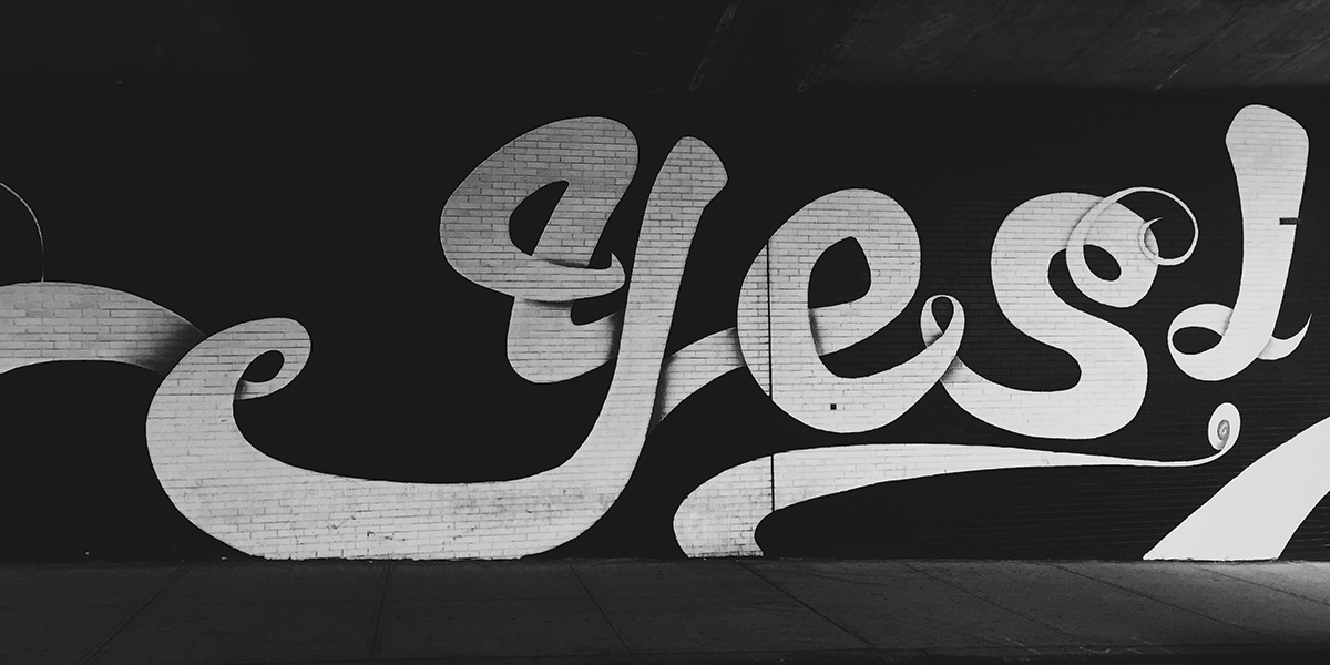 "Brick wall with graffiti that says ""yes"""